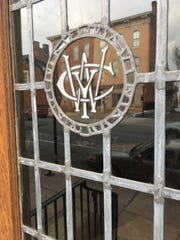 The East Market streetscape is reflected in the leaded glass entry door of the Woman's Club of York and bears the initials WCY.