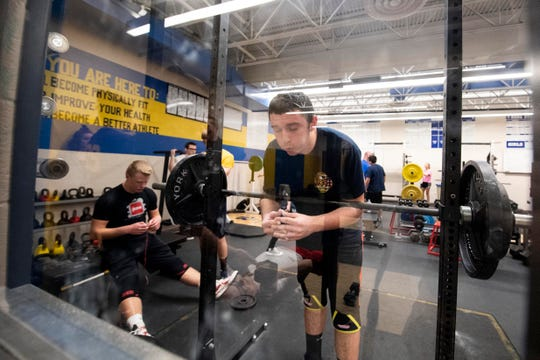 Patrick Maloney racks his weight after completing reps on a front squat, while Noah Hulslander, left, opens a fruit by the foot, his favorite post-workout snack, Wednesday, Dec. 12, 2018. The Rams' powerlifting team has won three state championships since starting the program in 2012.