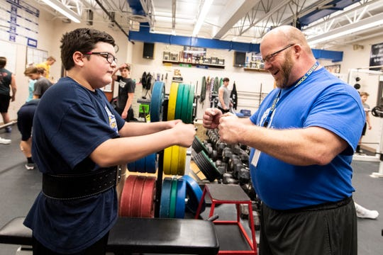 Kennard-Dale powerlifting head coach Niko Hulslander, right, fist bumps with sophomore Brian Rasmuson, following Rasmuson's personal record in squats, Wednesday, Dec. 12, 2018. Rasmuson has autism, but hasn't kept him from being competitive on the Rams' powerlifting team.