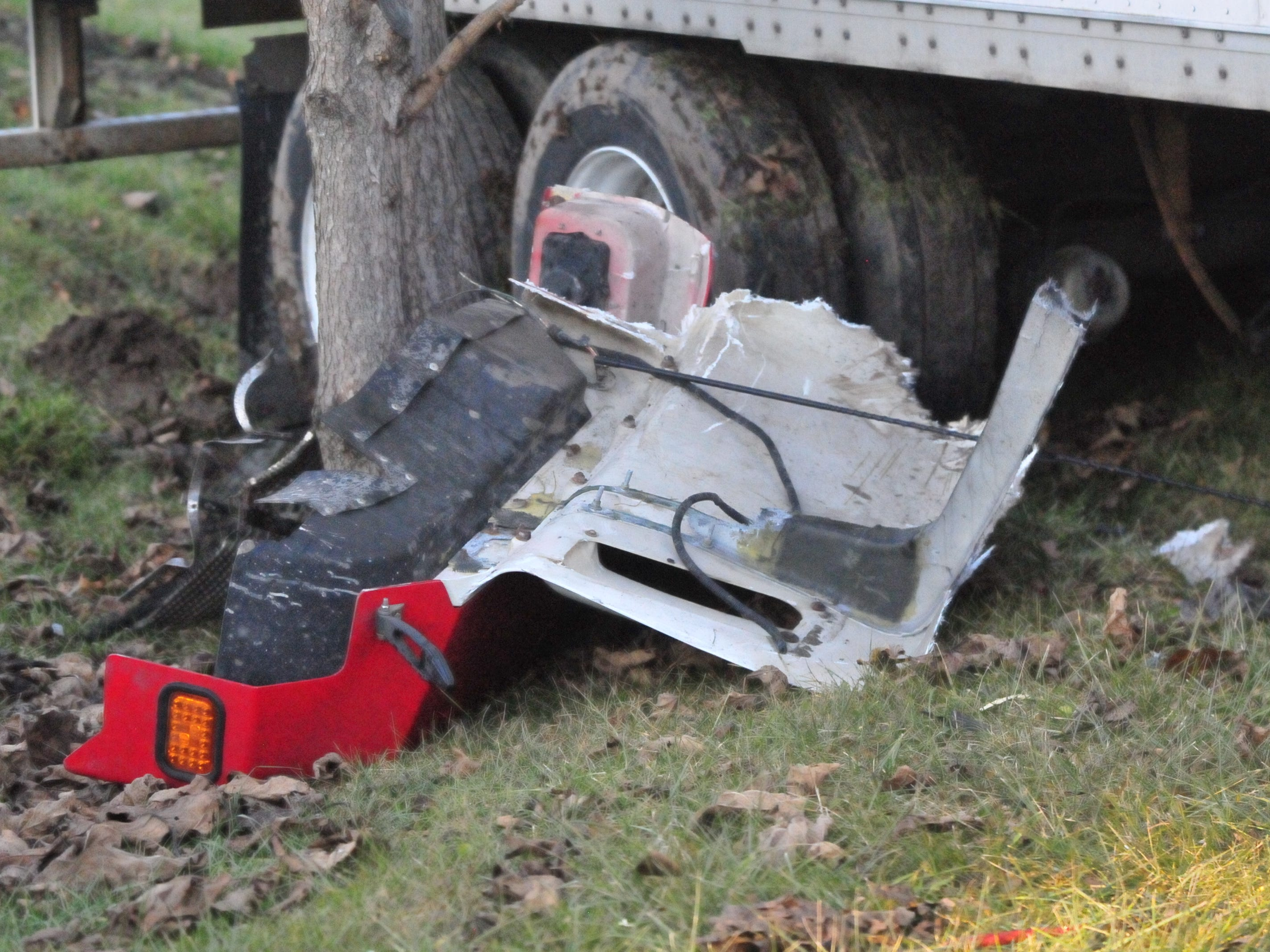 Pieces of a damaged semi tractor-trailer sit next to a tree and the semi's rear tires Monday afternoon.