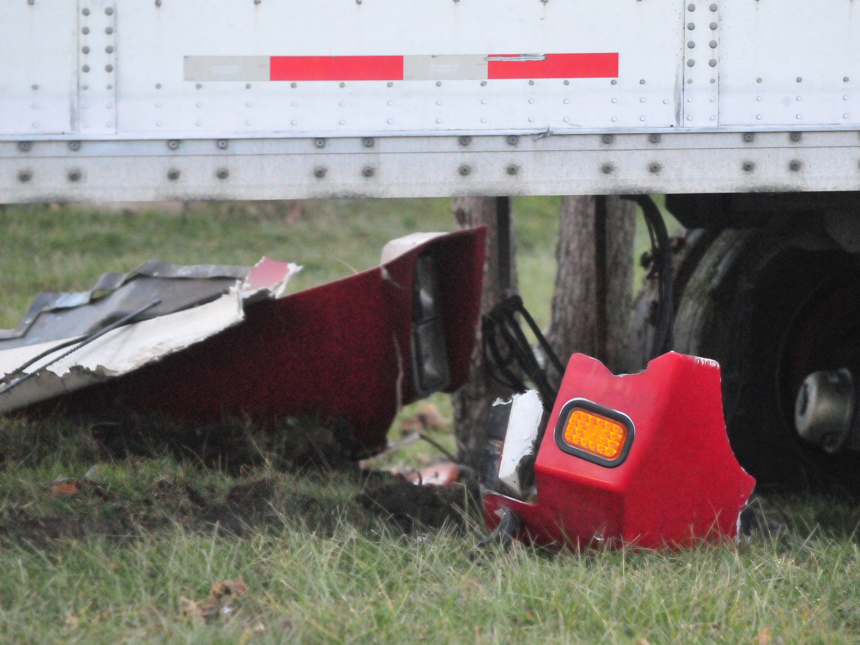 Parts of a damaged semi tractor-trailer sit in the grass adjacent to U.S. 35 after Monday afternoon's three-vehicle accident.