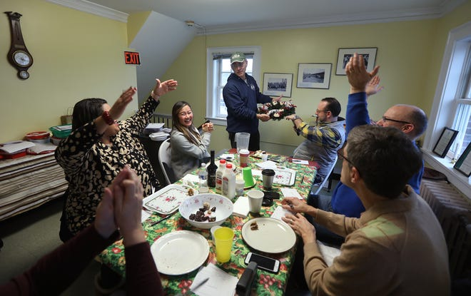 Evan Lowenstein, assistant market supervisor, holds up a tray of cookies that looked like ornaments on a wreath before serving them to the judges who applauded their presentation.  The judges were Daniele Lyman-Torres, commissioner of Recreation and Youth Services for the City of Rochester, Lihn Phillips, local food and drink blogger, Vince Press, freelance food writer, Adam Wilcox, freelance food writer, Michael Warren Thomas, radio host of WYSL 1040 AM, and just out of the frame Tracy Schuhmacher, food and drink writer at the Democrat and Chronicle.