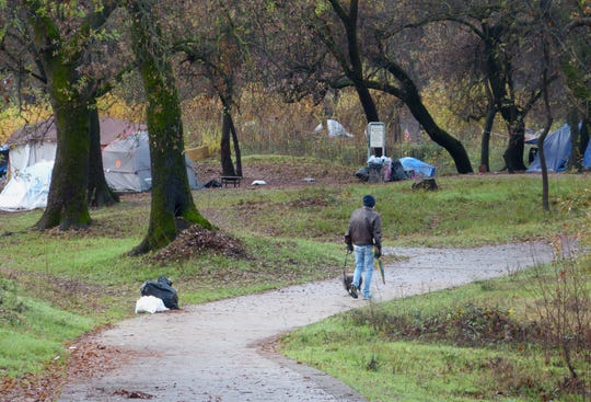 A man walks his dog Monday morning past a row of tents at the Parkview Riverfront Park in Redding.