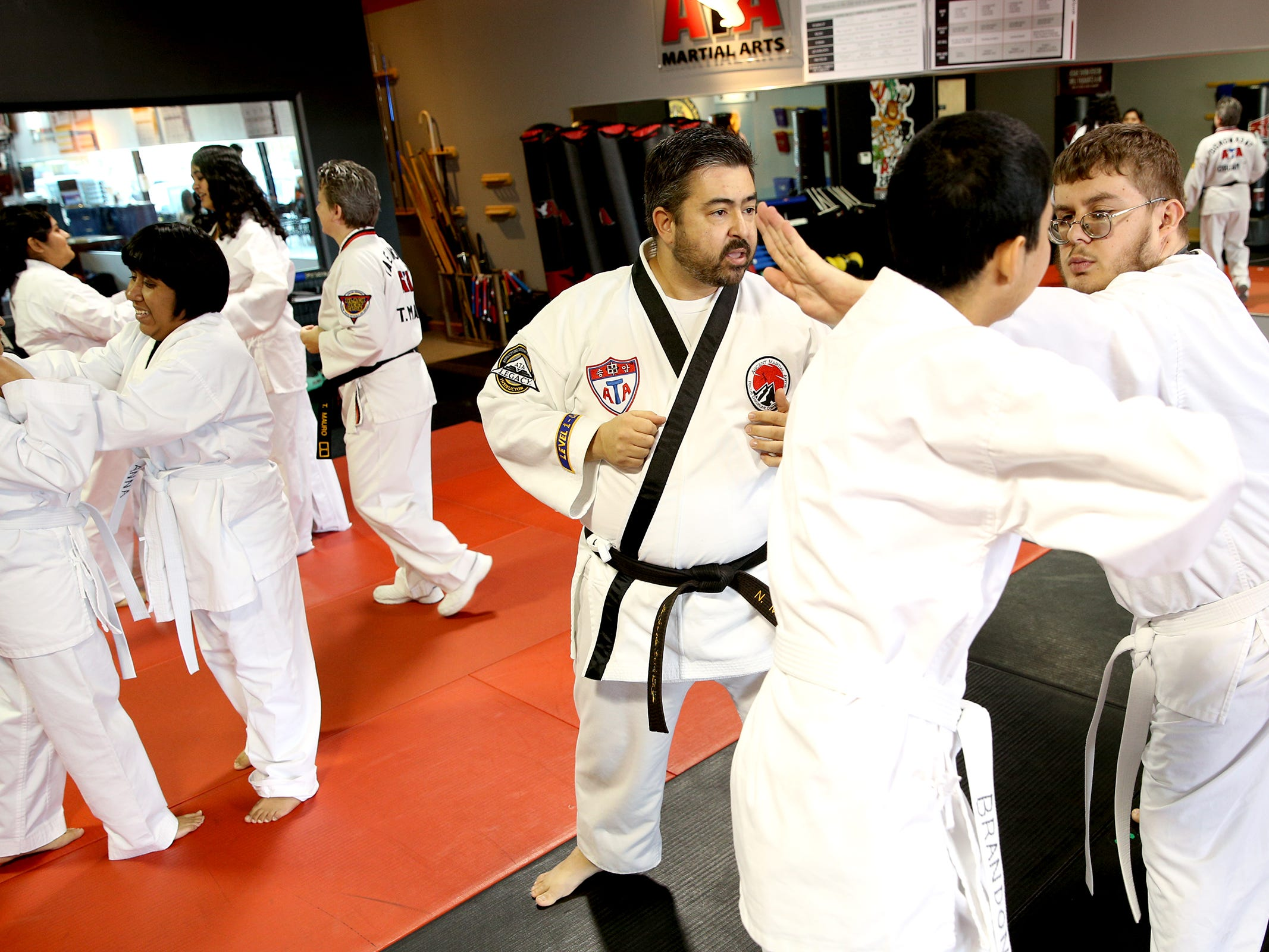 Martial arts instructor Nathaniel Mauro helps teach young adults with disabilities self-defense at ATA Martial Arts Keizer on Thursday, Dec.13, 2018.