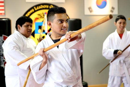 Abram Cortes practices using a bo staff, during a self-defense martial arts class, as part of a Woodburn School District transition program, at ATA Martial Arts Keizer on Thursday, Dec.13, 2018.