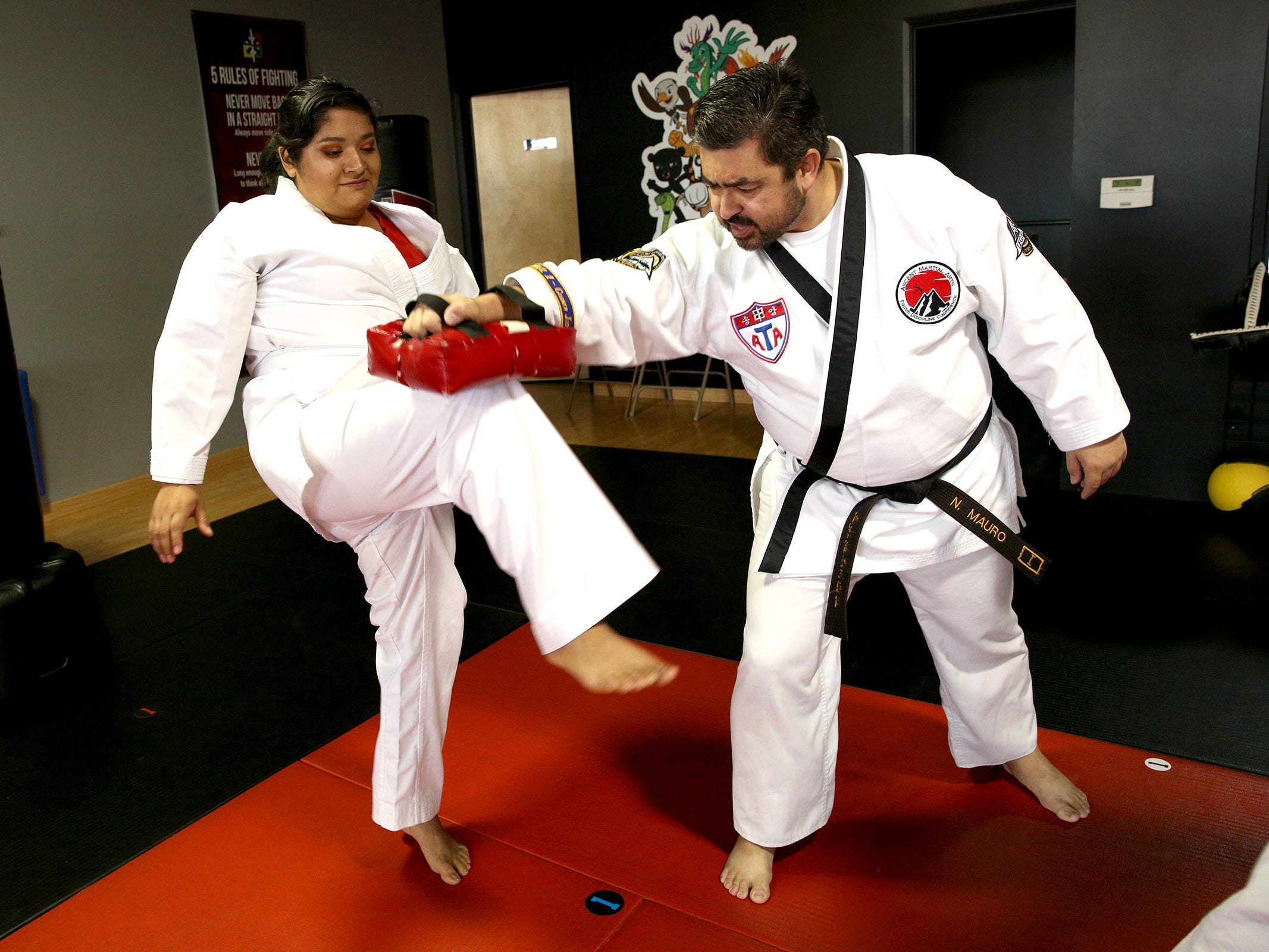 Martial arts instructor Nathaniel Mauro helps Esperanza Ramirez practice a knee exercise as part of a Woodburn School District transition program at ATA Martial Arts Keizer on Thursday, Dec.13, 2018.