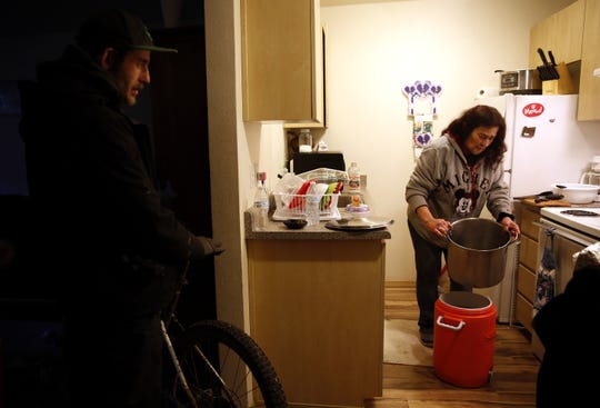 Joann (right) pours homemade turkey and rice soup into a portable container while talking with her son in her apartment in Salem, Oregon, on Saturday, Dec. 8, 2018. After more than five years homeless, Joann moved into her apartment in February through Salem's Homeless Rental Assistance Program.