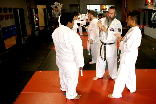 Director of Woodburn School District transition program, CJ High (center) helps teach students with disabilities self-defense at ATA Martial Arts Keizer on Thursday, Dec.13, 2018.