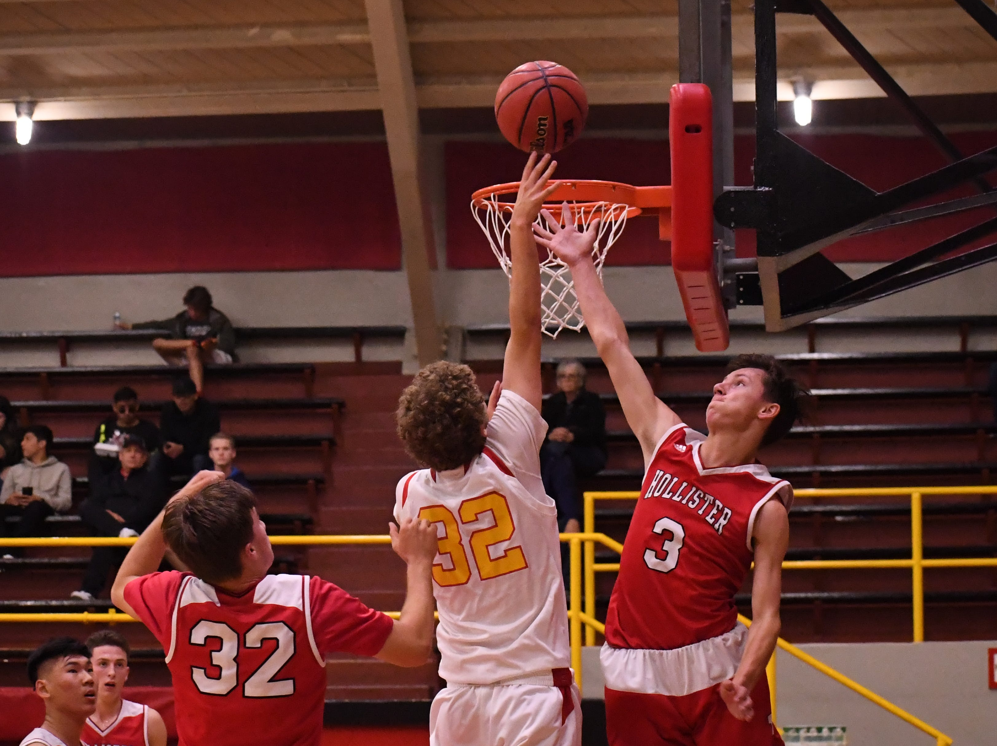 Palma forward Colin Neff (32) lays in a shot above the arm of a San Benito defender.