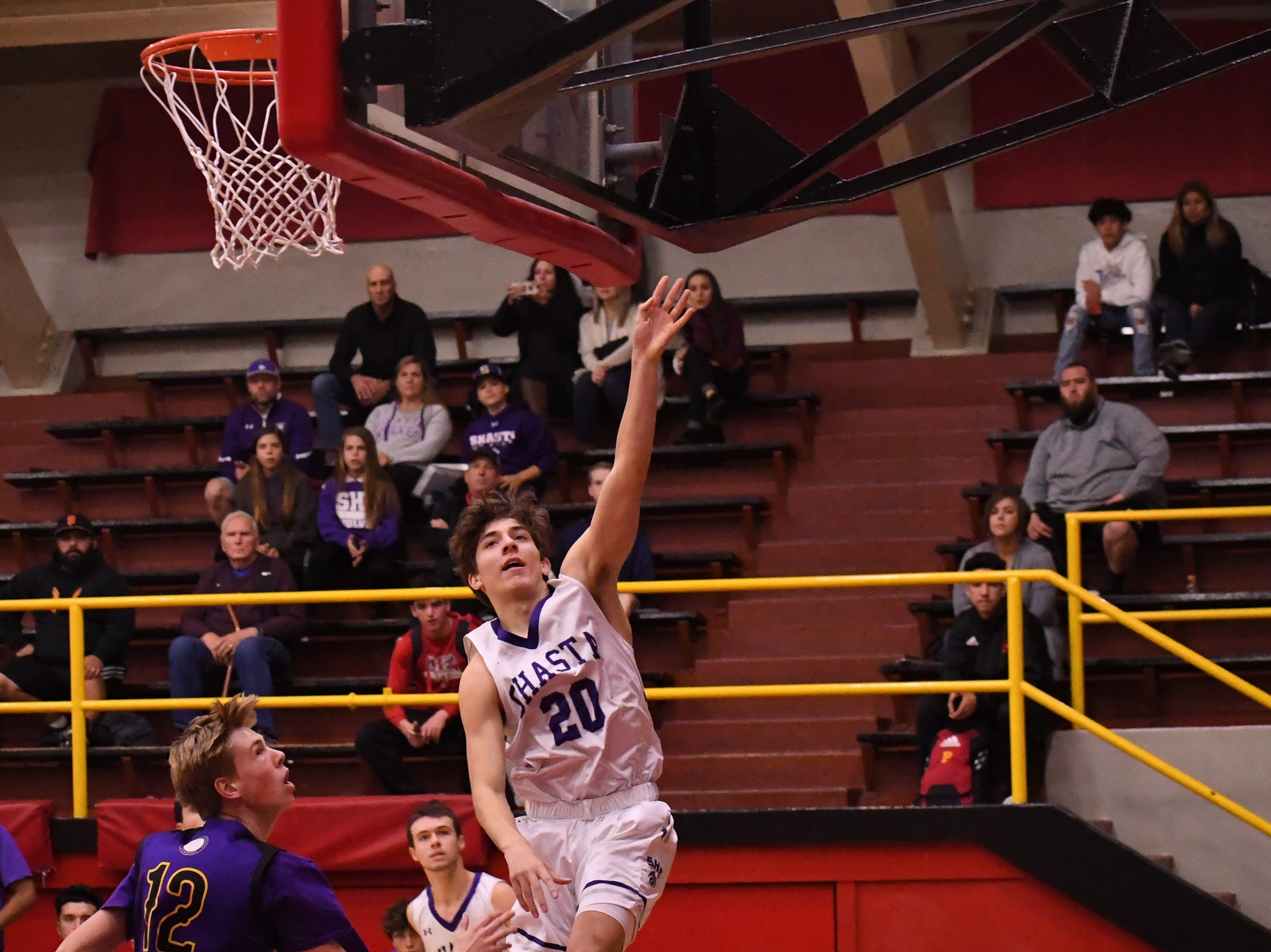 Shasta guard Caden Turner (20) falls away from the basket after scoring a layup.