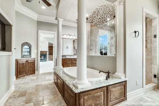 A spa-like bath features a columned soaking tub and a double-headed shower.