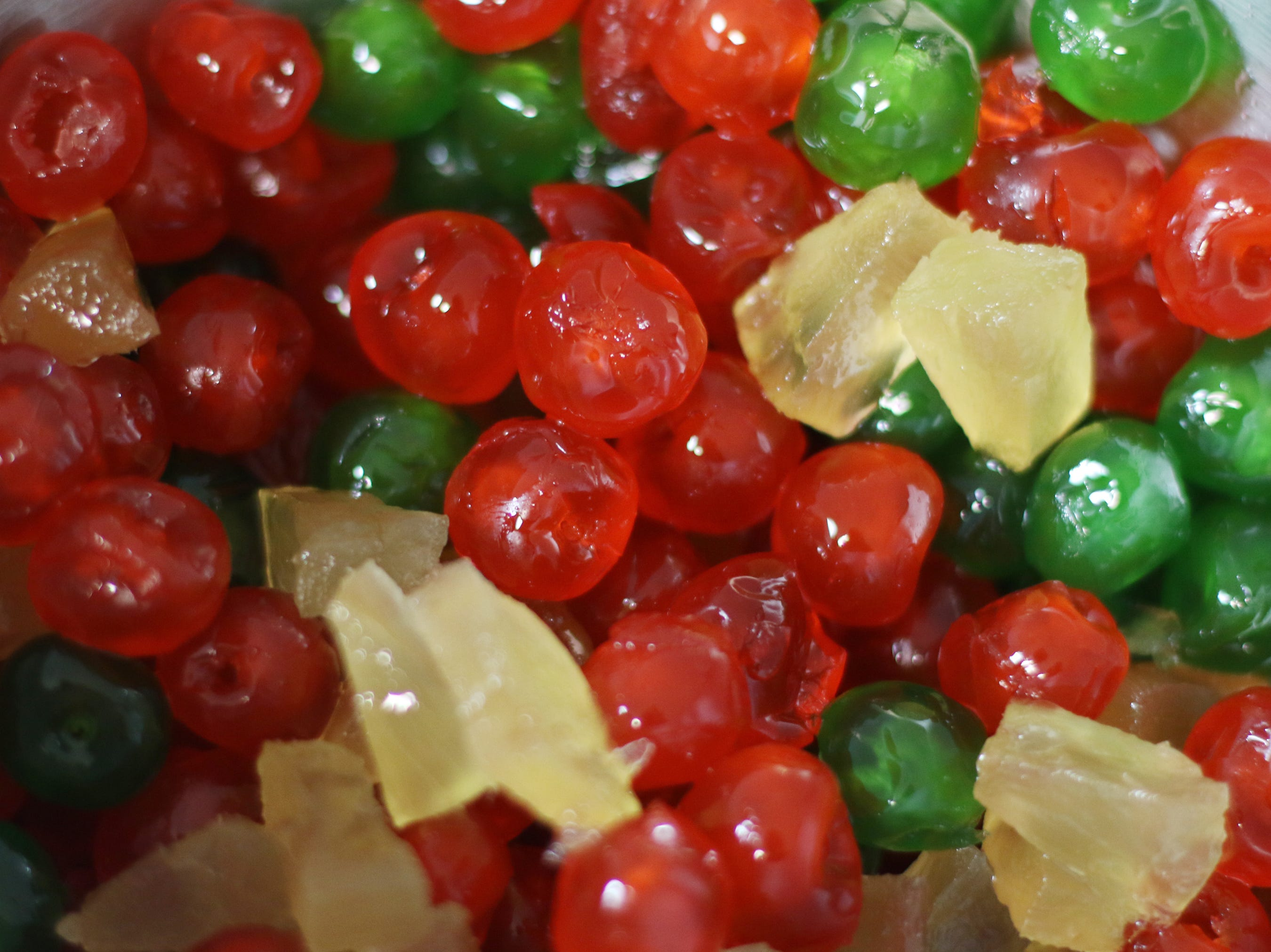 Candied fruits like these cherries and pineapple pieces became a traditional ingredient in a fruitcake because the high sugar content preserved the fruit. Shannon Tinsley, owner of SweetNanaCakes in Staunton, soaks the candied fruit in brandy and rum before baking it in a fruitcake.