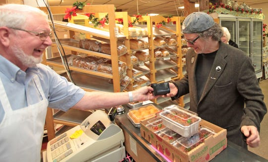 Paul Cline makes his annual pilgrimage to buy fruitcakes from David Miller at Miller's Bake Shoppe in Stuarts Draft. The bakery has been selling dozens of the traditional cakes every holiday season.