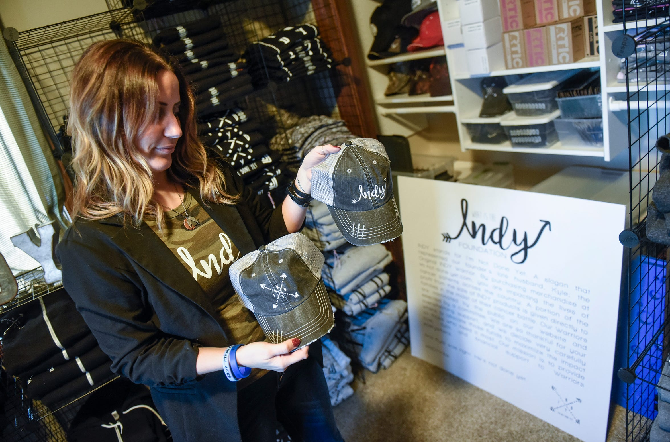 INDY Foundation founder Kayla Strand holds items sold to support the work of the foundation during an interview Thursday, Dec. 13, at her home.