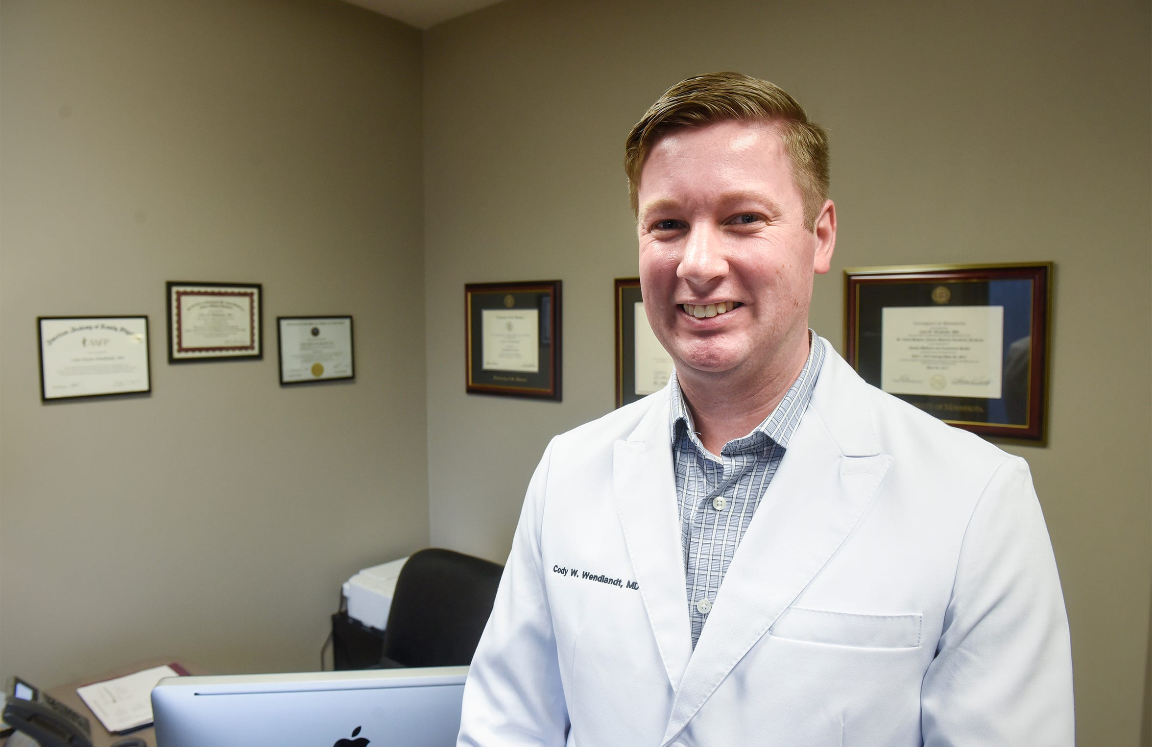 Dr. Cody Wendlandt smiles for a photograph Monday, Dec. 10, at Sartell Family Medicine in Sartell.