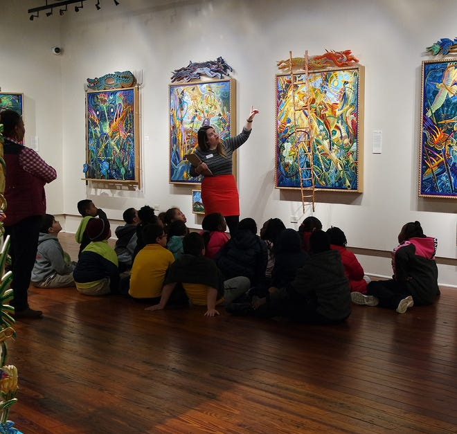 Anissa Ford, Education Director at Gadsden Arts, talks with students from Greensboro Elementary School to interpret the meaning of a painting by Mark Messersmith.