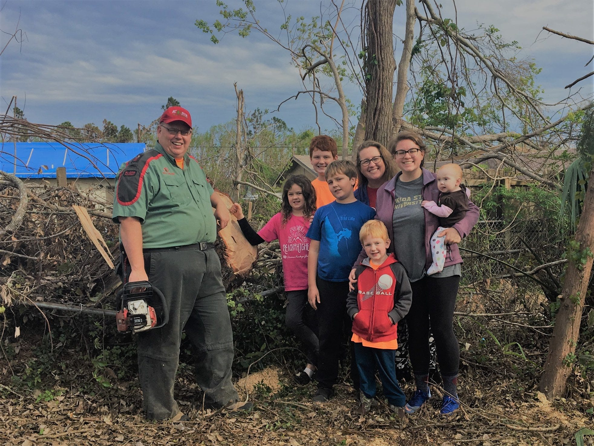 Melanie and Tony Gillespie and their six kids pose for a photo as they clean the yard of a Panama City resident after Hurricane Michael on Thanskgiving.