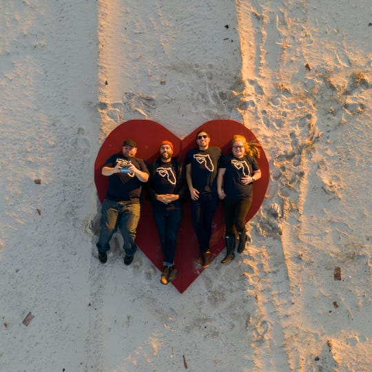 Jonathan Smith, Jeremy Cowart, Alex Workman & Chelsea Workman are photographed from above, on the heart that represents the Never Forgotten project.