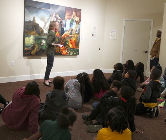 Grace Robinson, Executive Director at the Gadsden Arts Center & Museum guides students in determining the story behind this painting by Carrie Ann Baade.