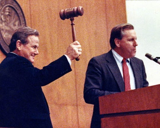 It looks like Florida House Speaker T K Wetherell is about to be bashed in the head by Rep. Elvin Martinez, D-Tampa, but the assault is just a distortion by a camera lens. Actually Rep. Martinez was helping the Speaker gavel a bill to completion in the chamber in April 1991.