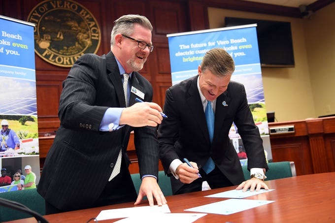 City of Vero Beach Mayor Harry Howle (left) and Eric Silagy, president of Florida Power & Light Co., share a laugh Monday, Dec. 17, 2018 as they sign the final paper work for the sale of the Vero Beach electric system to FPL during a public ceremony at City Hall in Vero Beach. The $185 million purchase of the Vero Beach electric system was more than a decade in the making.