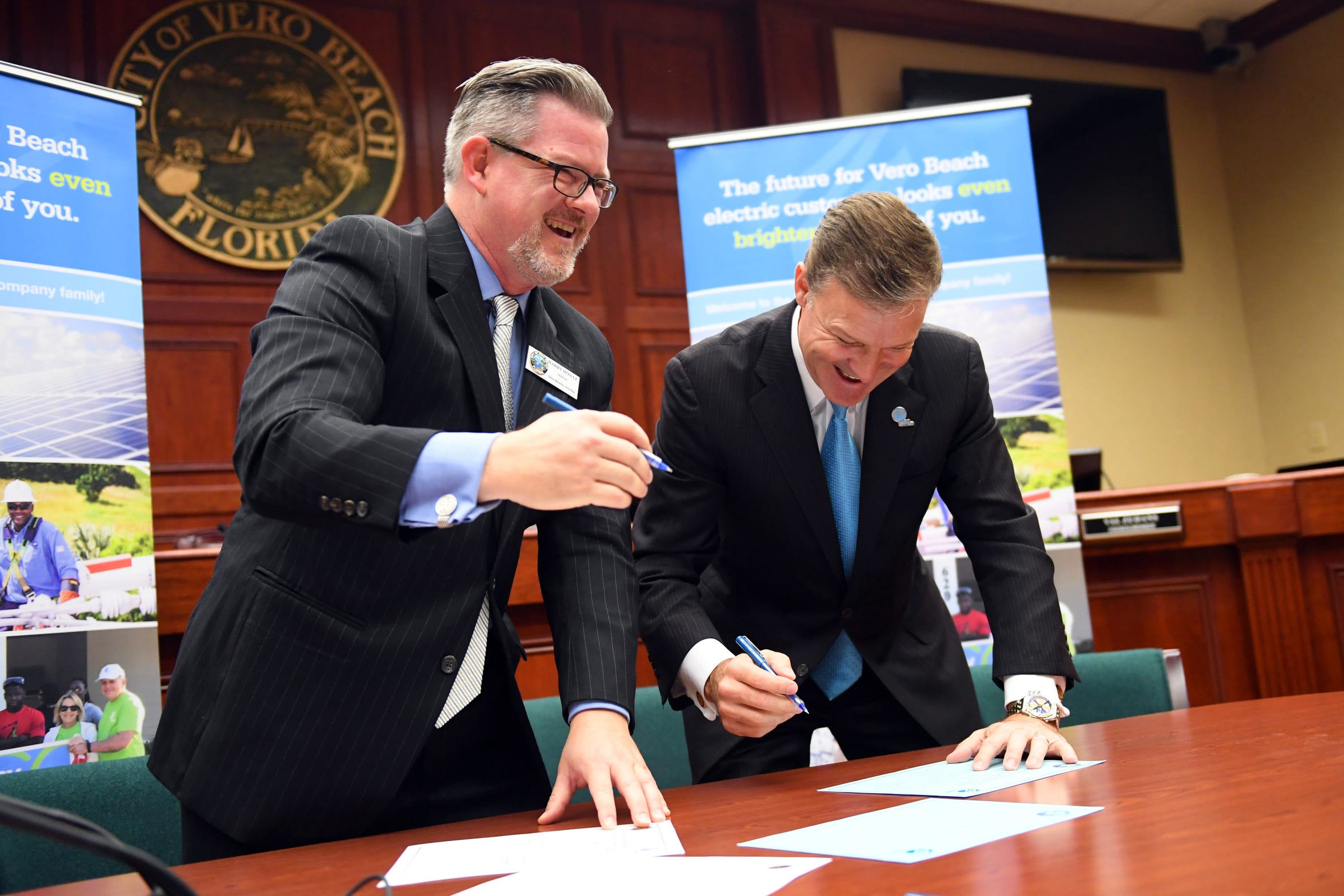 City of Vero Beach Mayor Harry Howle (left) and Eric Silagy, president of Florida Power & Light Co., share a laugh Dec. 17, 2018, as they sign the final paper work for the sale of the Vero Beach electric system to FPL during a public ceremony at City Hall in Vero Beach.