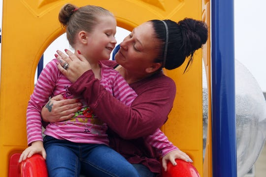 """Ericka Gianini plays with her daughter Kayleani, 6, on the playground near their Fort Pierce home on Saturday, Dec. 15, 2018. Gianini had the opportunity to travel to Connecticut for Christmas to see her oldest daughter, Gabriella, who she hasn't seen in six years because of an addition to opioids. """"Going to rehab was the easy part,"""" said Gianini, who is now two years sober and is a manager at her job. """"But being away from (Gabriella), I'd cry every day."""""""