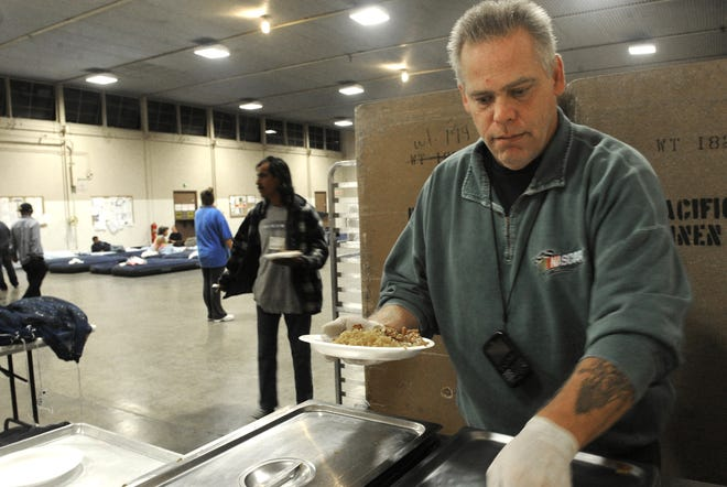 Volunteer Bob Walzer serves food for the homeless at the National Guard Armory. This photo was taken in 2012 when the winter shelter was in Oxnard.