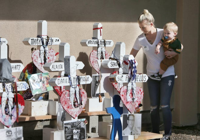 Borderline Bar & Grill employee Lacy Fuller, holding her son Waylon, helps organize items from the Borderline memorial that was moved Sunday from Moorpark Road and Rolling Oaks Drive to a new location near the entrance to the bar.