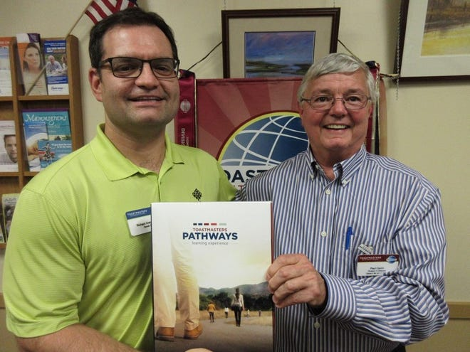 Richard Kretschmer (left), vice president of education for Speak E-Z in Millville, receives the new Pathways program from Paul Caron, Pathways Ambassador for Toastmasters International.