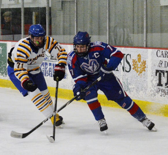 Mahopac forward T.J.  McKee battles Carmel forward Steven Mount for the puck heading into the corner during the first period on Sunday at Brewster Ice Arena.  The Indians won 9-7.