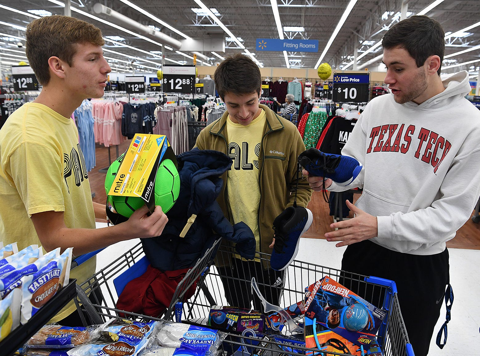 Burkburnett High School PALS students Sloan Lewis, left, Landon Boddy and Gavin Morris, right, talk about items they found on the wish lists of kids staying at the Childrens Aid Society Childrens Home. The PALS work with the Wichita Falls Police Officers Association each year on the project.