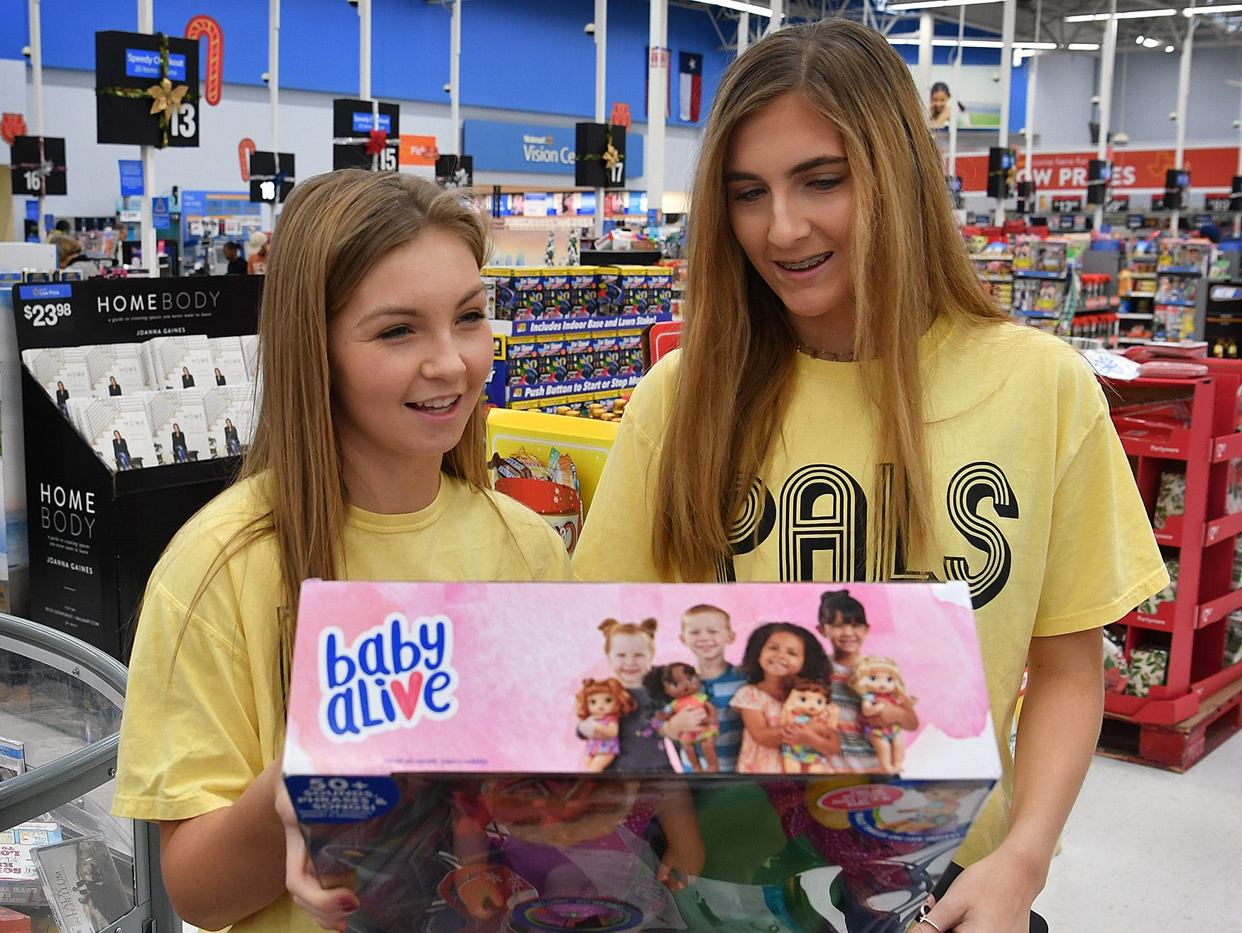 Burkburnett High School PALS members Tayler Tournay, left, and Lauren Johnston look over some of the gifts they picked for children living at the Childrens Aid Society Childrens Home during a shopping trip with the Wichita Falls Police Officers Association Monday.