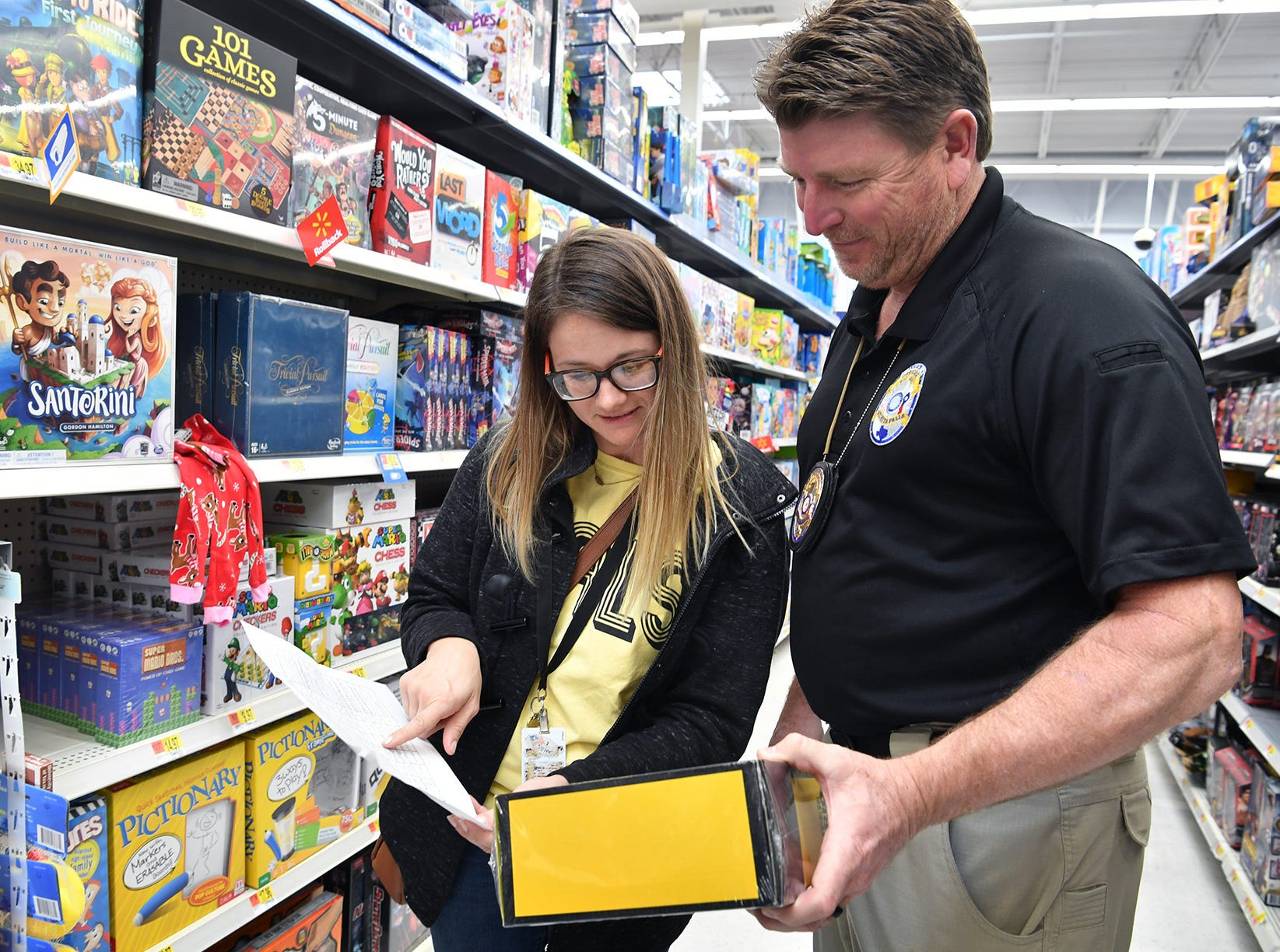 Burkburnett High School teacher Brittany Andrajack and Wichita Falls Police officer Kelly Brunson look over a list of gift items as they help BHS PALS students Christmas shop for kids staying at the Childrens Home Monday.