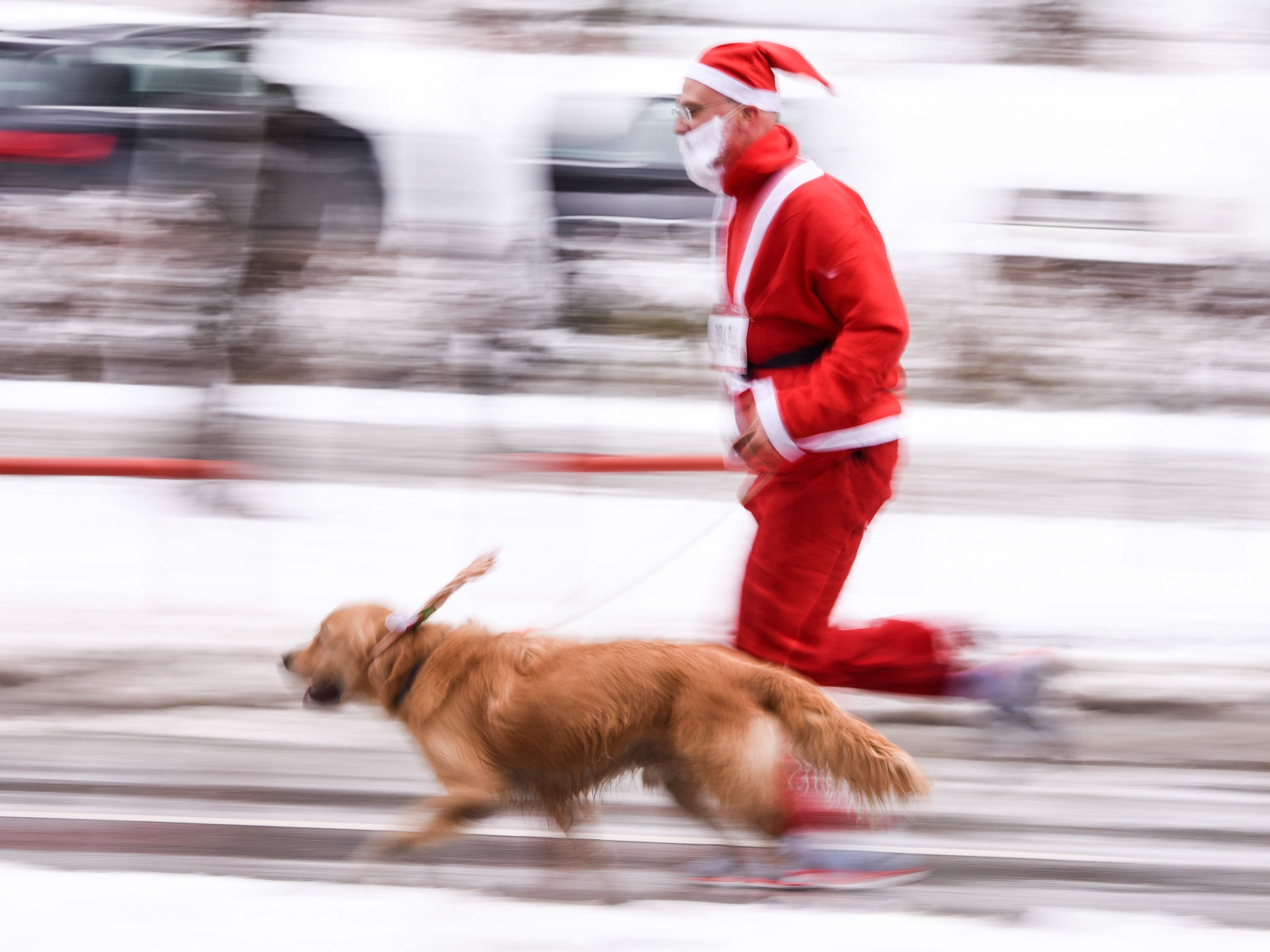 A man dressed as Santa Claus runs with his dog as he takes part in a charity race in Pristina, Kosovo, Dec. 16, 2018 to raise money for families in need.