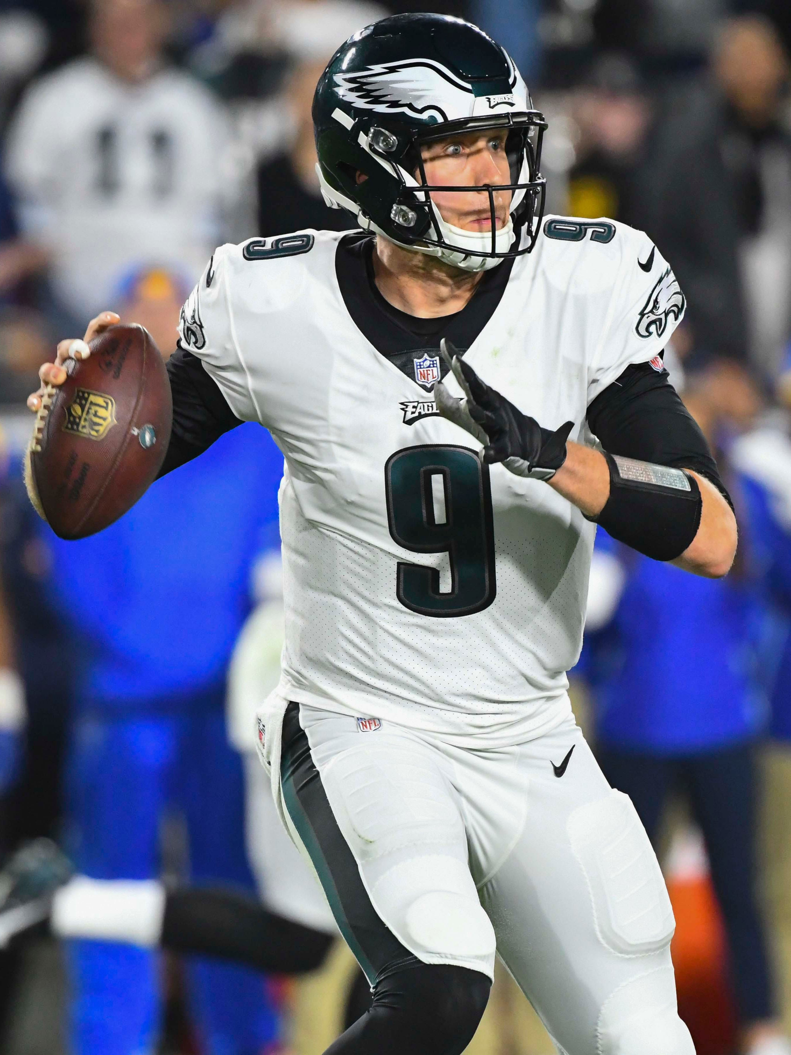 Eagles quarterback Nick Foles rolls out to avoid the pass rush against the Rams.