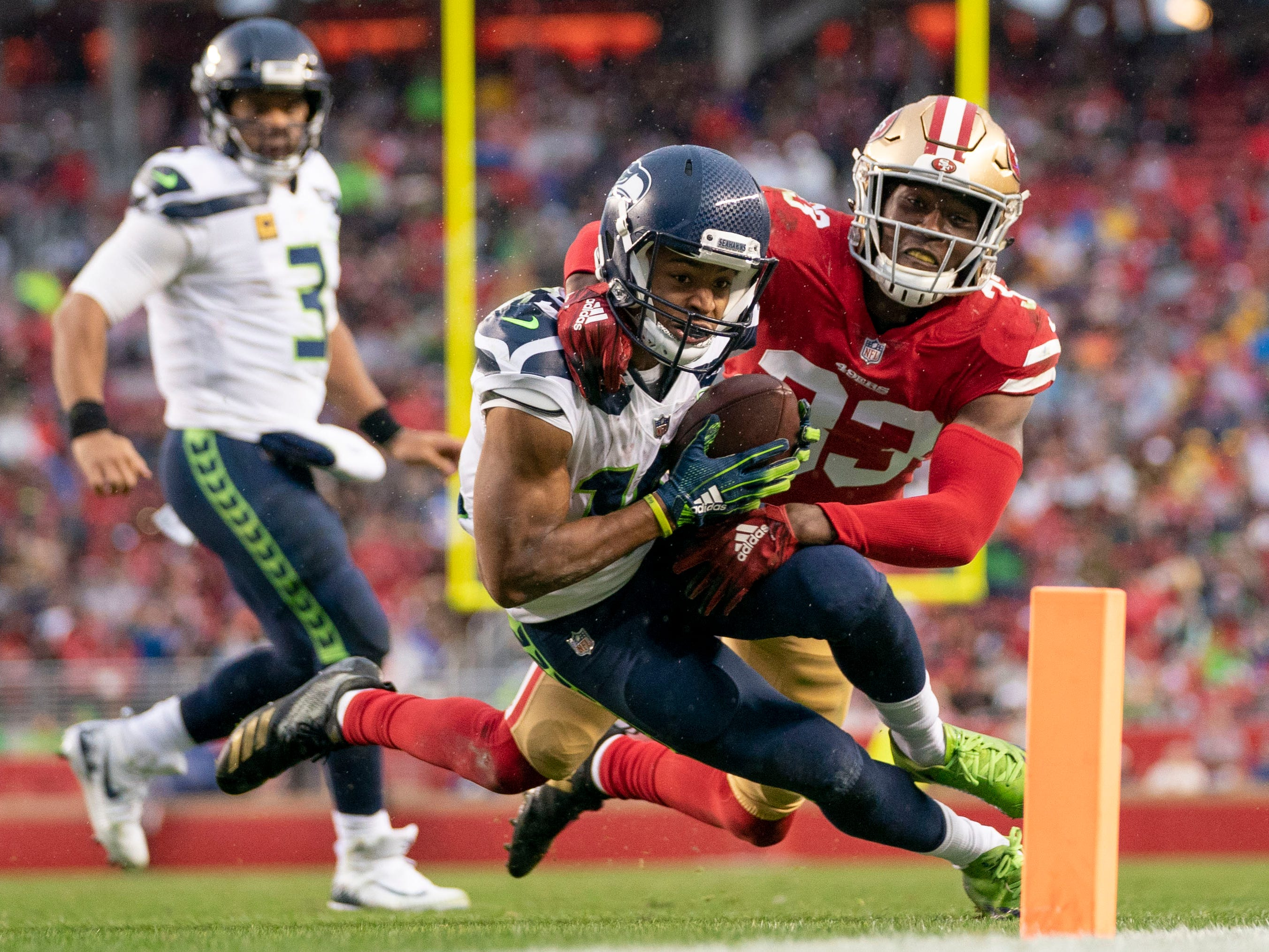 Week 15: Seattle Seahawks wide receiver Tyler Lockett is tackled by San Francisco 49ers defensive back Tarvarius Moore during the third quarter at Levi's Stadium. The 49ers won the game, 26-23, in overtime.