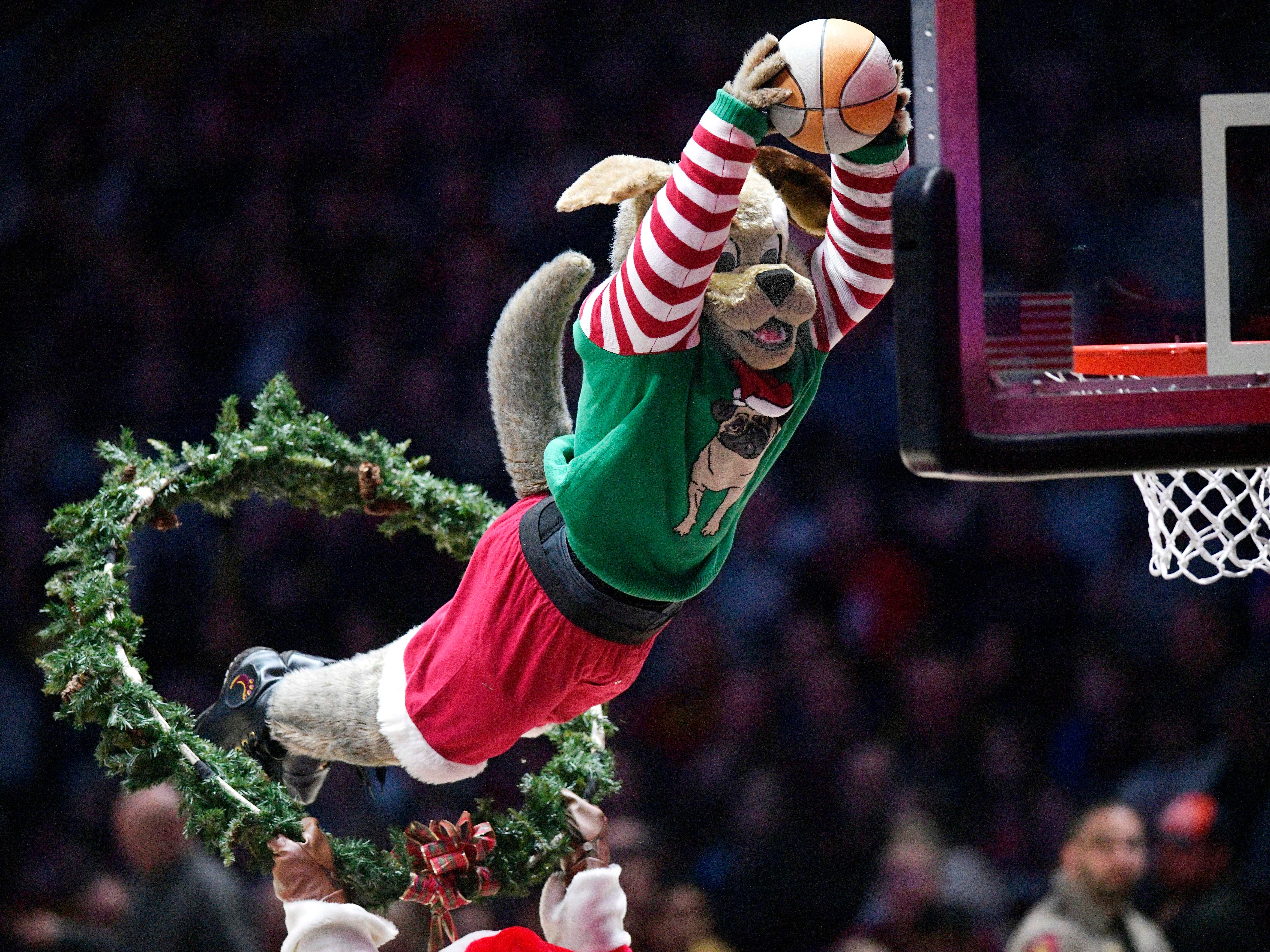 Dec. 16: Cavaliers mascot Moondog leaps through a wreath for a festive slam.