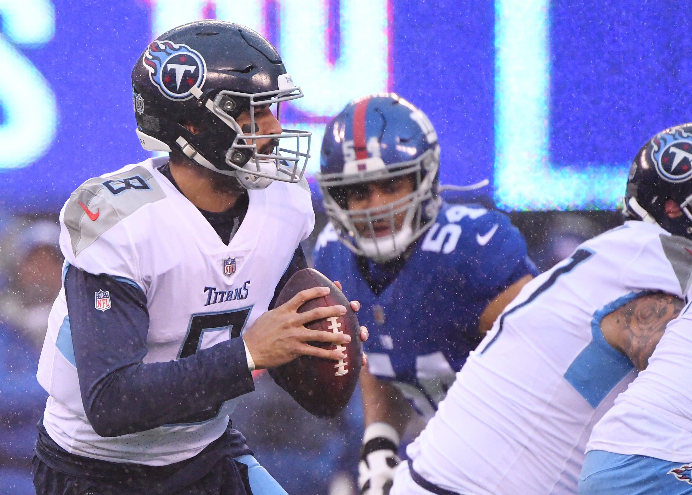 Week 15: Tennessee Titans quarterback Marcus Mariota rolls out to pass against the New York Giants in the rain at MetLife Stadium. The Titans won the game, 17-0.