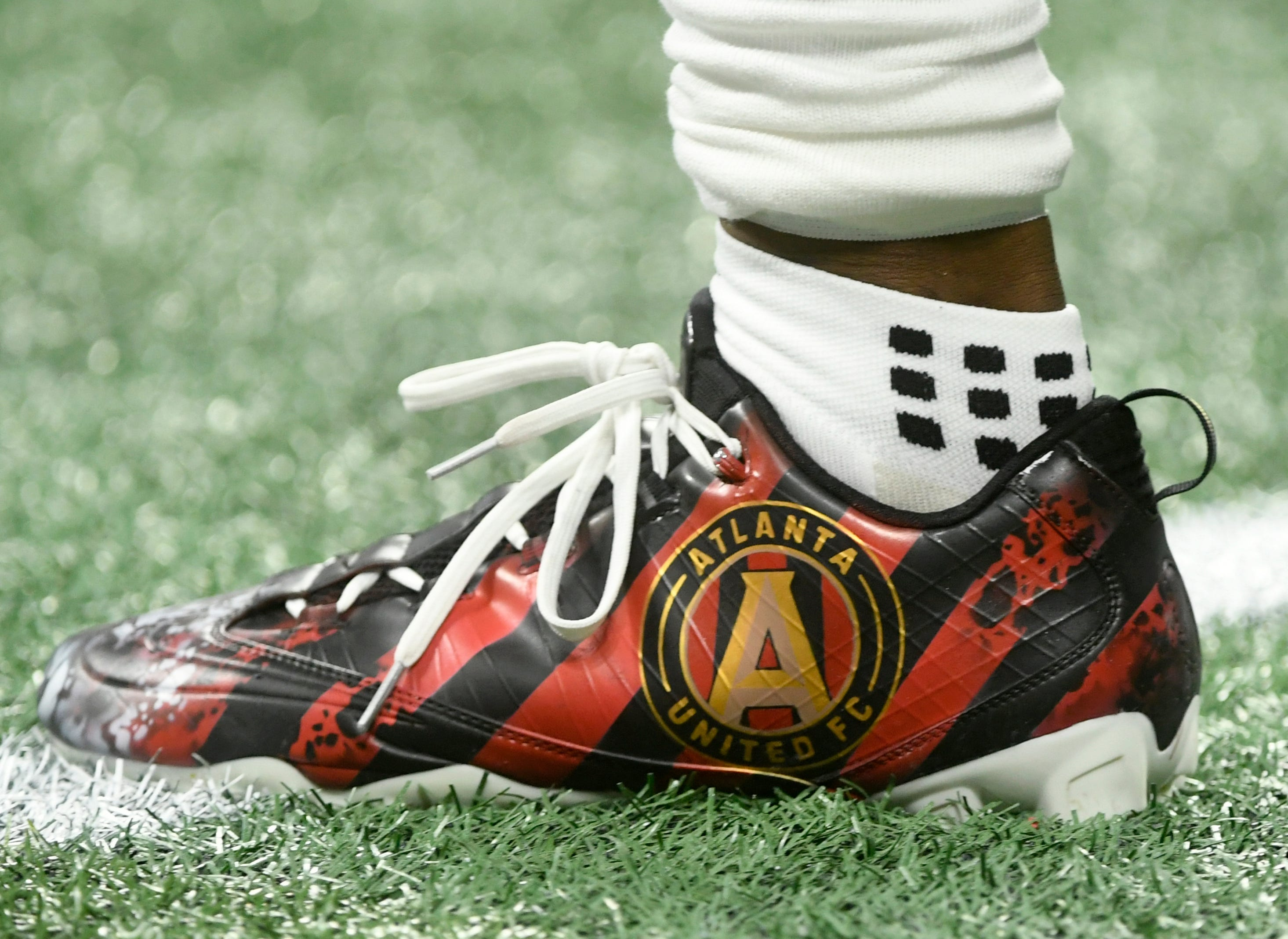 Atlanta Falcons wide receiver Mohamed Sanu wears shoes featuring the logo of Atlanta United FC, the 2018 Major League Soccer champions.
