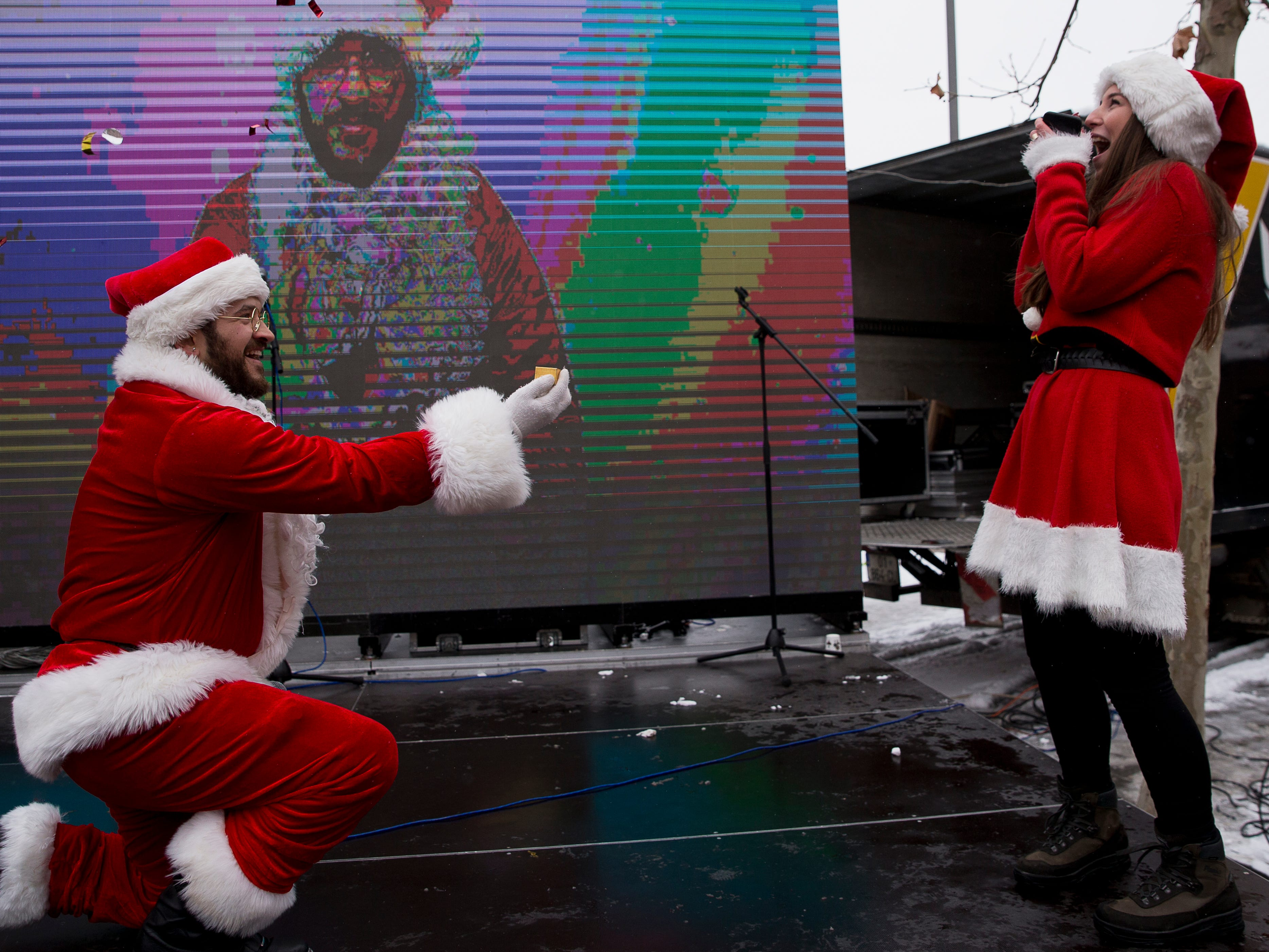 Jusuf Islami proposes to his partner Hana participating in the third Santa Claus run in Kosovo capital Pristina on Sunday, Dec. 16, 2018. Hundreds runners participated in a charity Santa Claus race to raise funds for families in need in Kosovo.