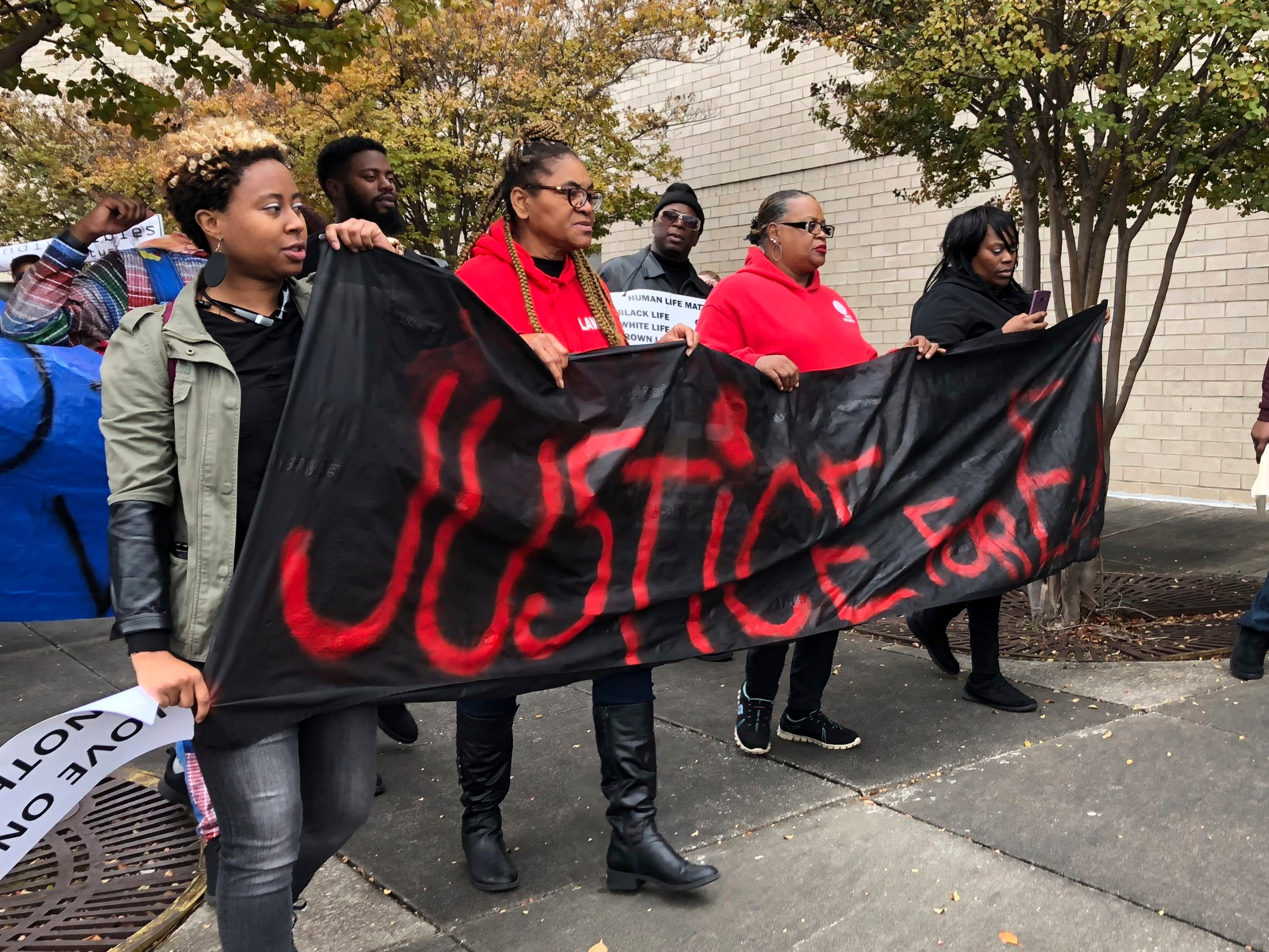 """Protestors carry a sign reading """"Justice for E.J."""" during a protest at the Riverchase Galleria mall in Alabama on Saturday, Nov. 24, 2018."""