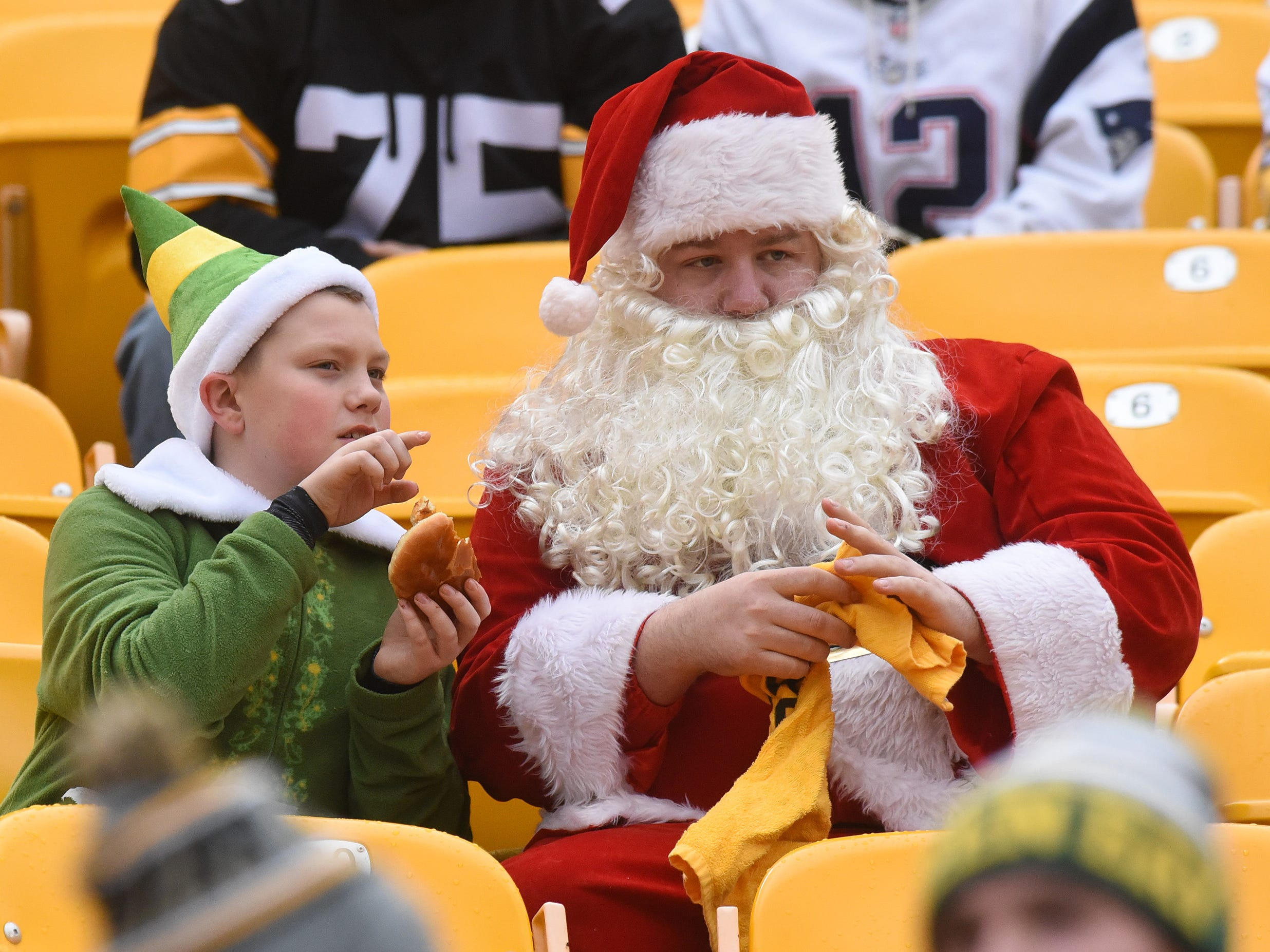 People dressed as Santa and a helper watch watch warmups before a game between the New England Patriots and Pittsburgh Steelers, Dec. 16, 2018, in Pittsburgh.