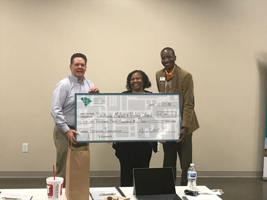 Gloria Brown, the winner of Feeding Innovation Anderson, poses for a picture with Brendan Buttimer and James Chatfield of the South Carolina Community Loan Fund.