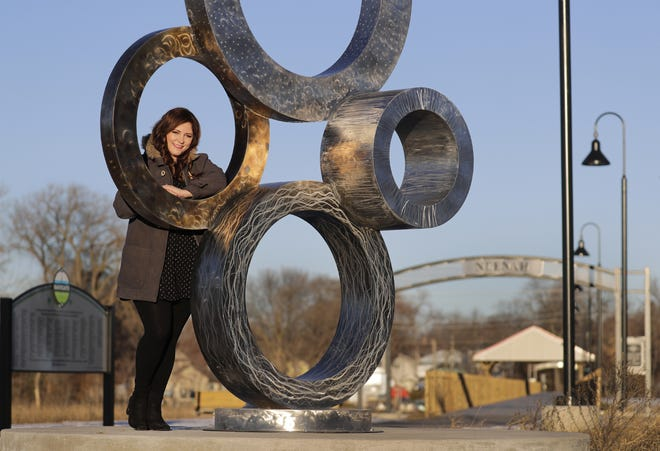 Amy Barker, former executive director of Future Neenah, stands by artwork along the Loop the Lake recreational trail in Neenah. Barker led the effort to raise more than $1 million in private funds for the trail.