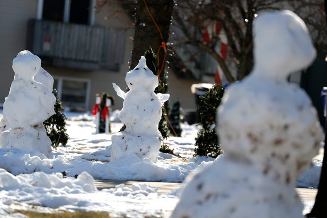 Snowmen slowly melt Tuesday in the yards of homes on South Clara Street in Appleton. Temperatures have climbed into the 40s this week.