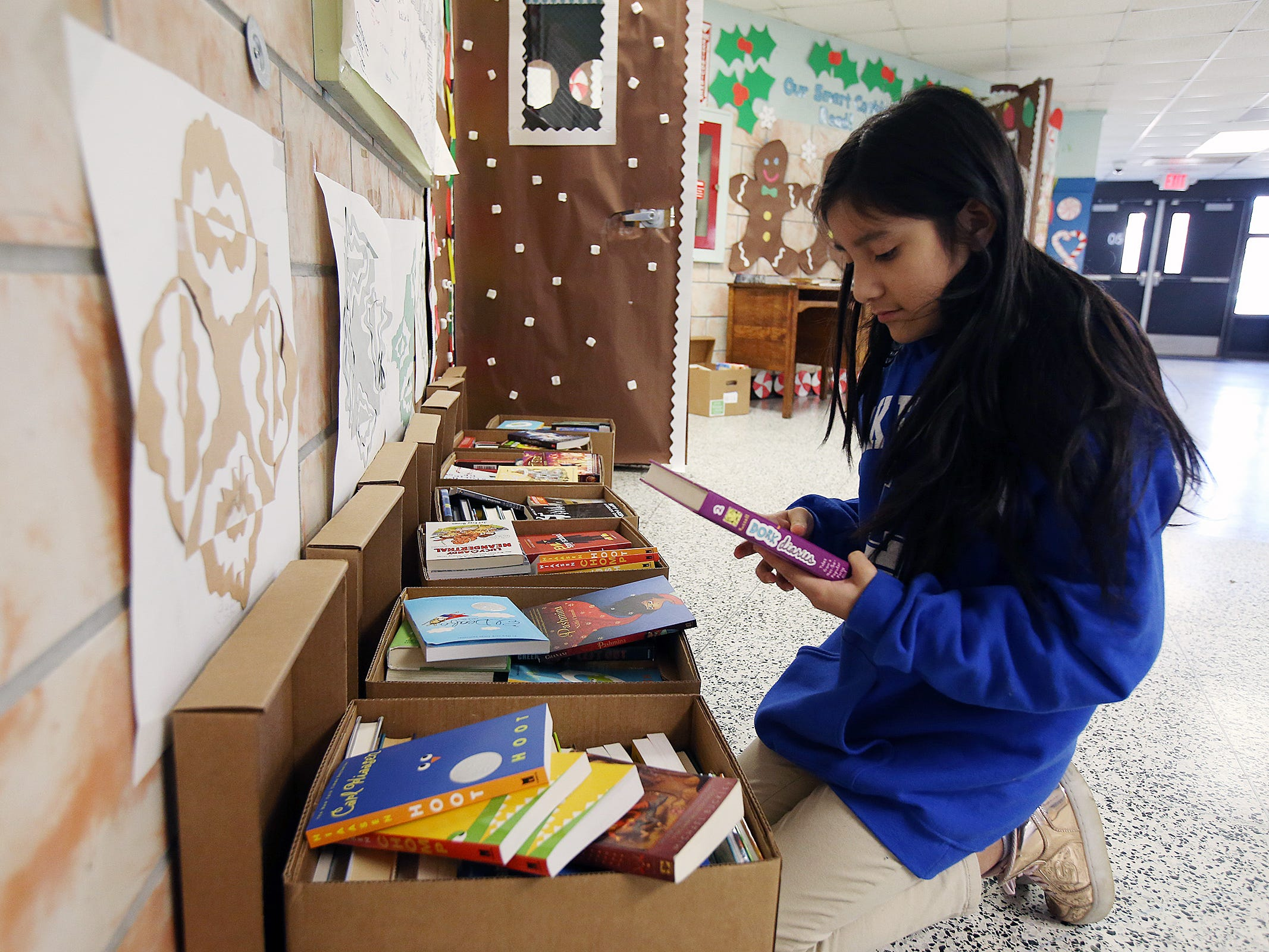 Ingrid Garcia, 11, of Lakewood chooses a book during a Bridge of Books Foundation event for sixth graders at Lakewood Middle School in Lakewood, NJ Tuesday, December 18, 2018. The Bridge of Books Foundation, which donates recreational reading books to underprivileged kids across the state, donated its one millionth book during this event.