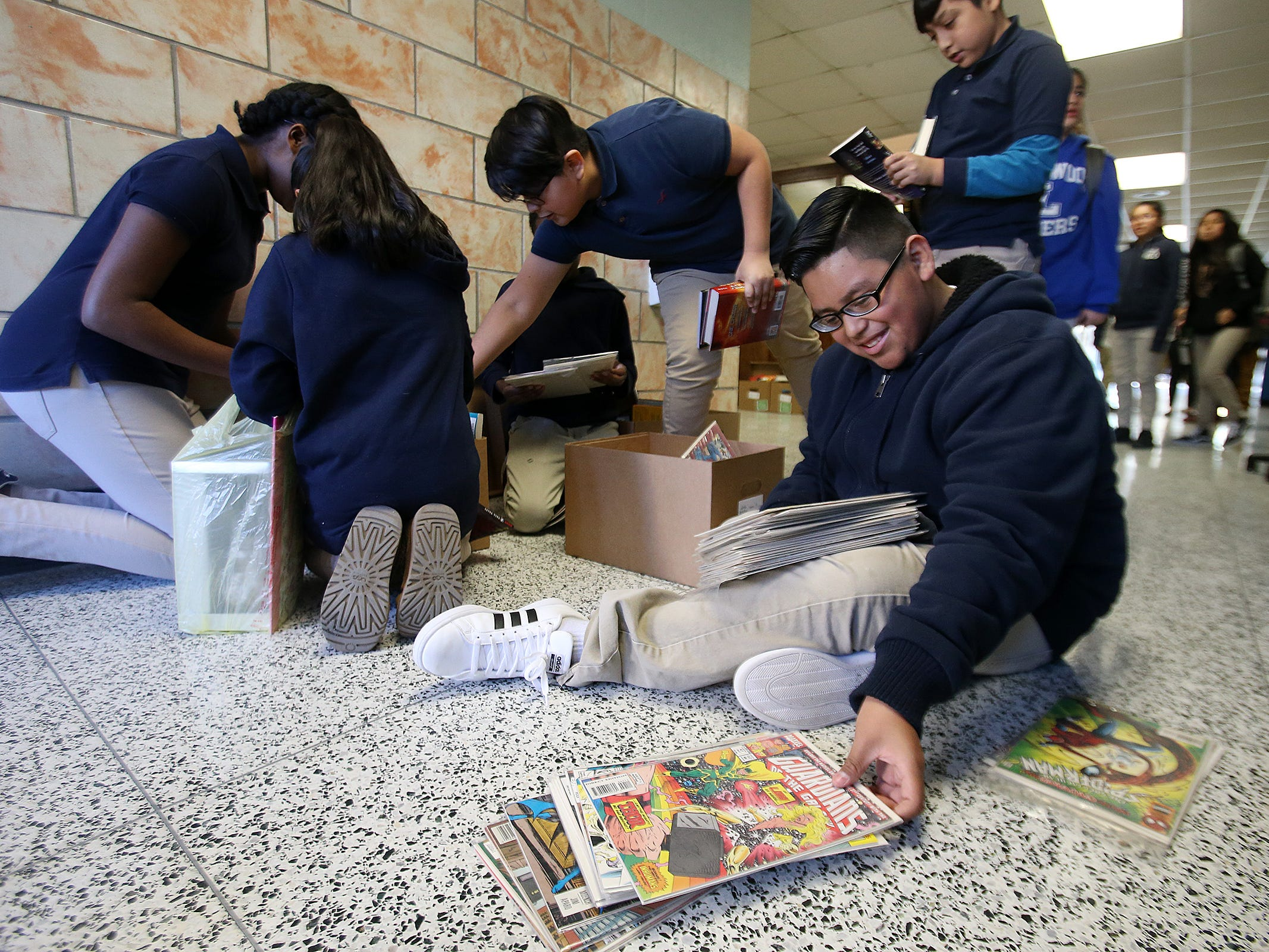 Fernando Morales, 12, of Lakewood chooses a comic book during a Bridge of Books Foundation event for sixth graders at Lakewood Middle School in Lakewood, NJ Tuesday, December 18, 2018. The Bridge of Books Foundation, which donates recreational reading books to underprivileged kids across the state, donated its one millionth book during this event.