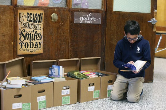 Luis Rosas, 11, of Lakewood chooses a book during a Bridge of Books Foundation event for sixth graders at Lakewood Middle School in Lakewood, NJ Tuesday, December 18, 2018. The Bridge of Books Foundation, which donates recreational reading books to underprivileged kids across the state, donated its one millionth book during this event.
