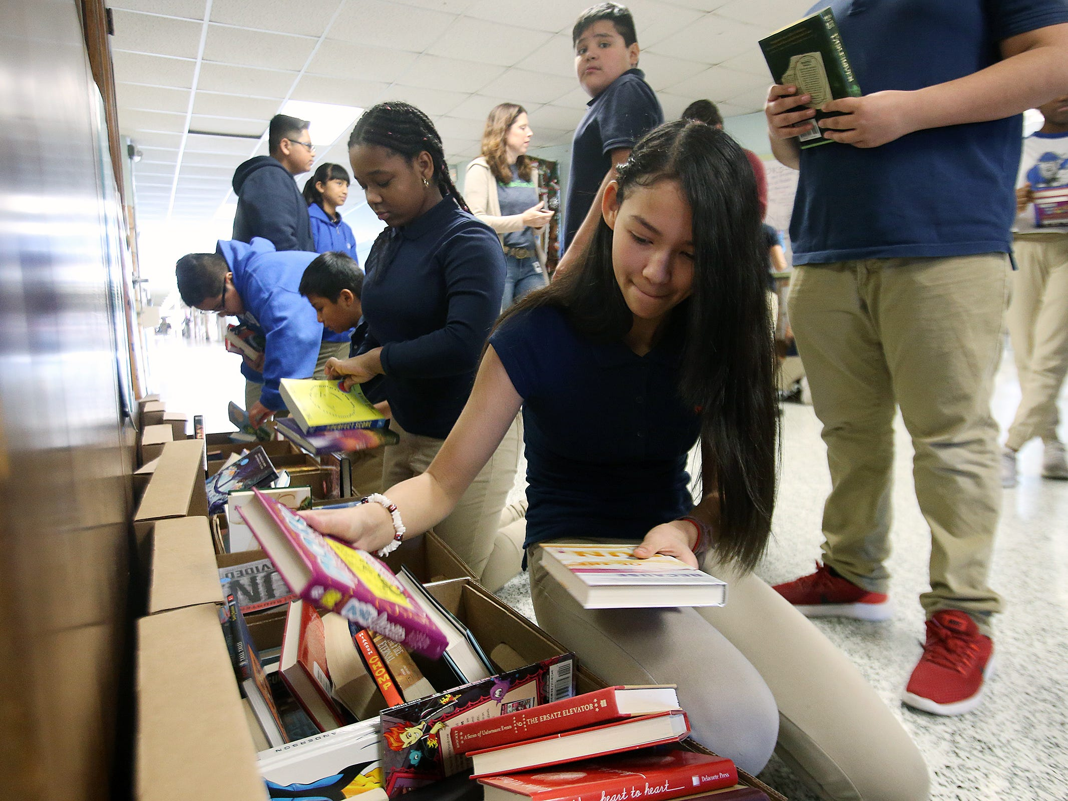 Angela Bui, 12, of Lakewood chooses a book during a Bridge of Books Foundation event for sixth graders at Lakewood Middle School in Lakewood, NJ Tuesday, December 18, 2018. The Bridge of Books Foundation, which donates recreational reading books to underprivileged kids across the state, donated its one millionth book during this event.